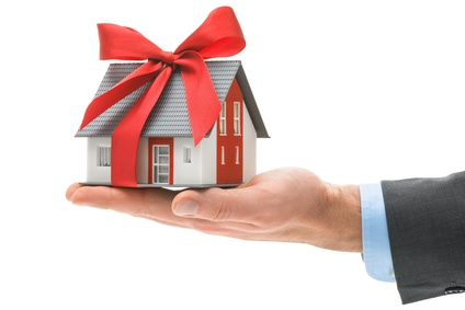 Real estate agent holds architectural model with red bow